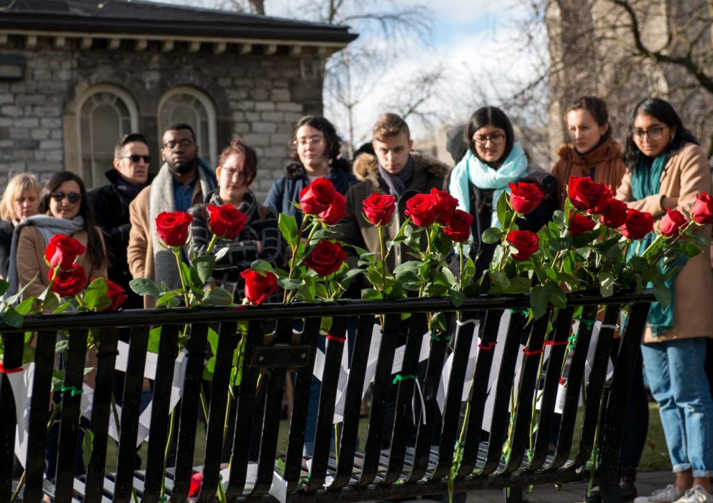A small crowd gathers to lay roses on the memorial bench in honour of the 14 women killed in the 1989 Montreal Massacre