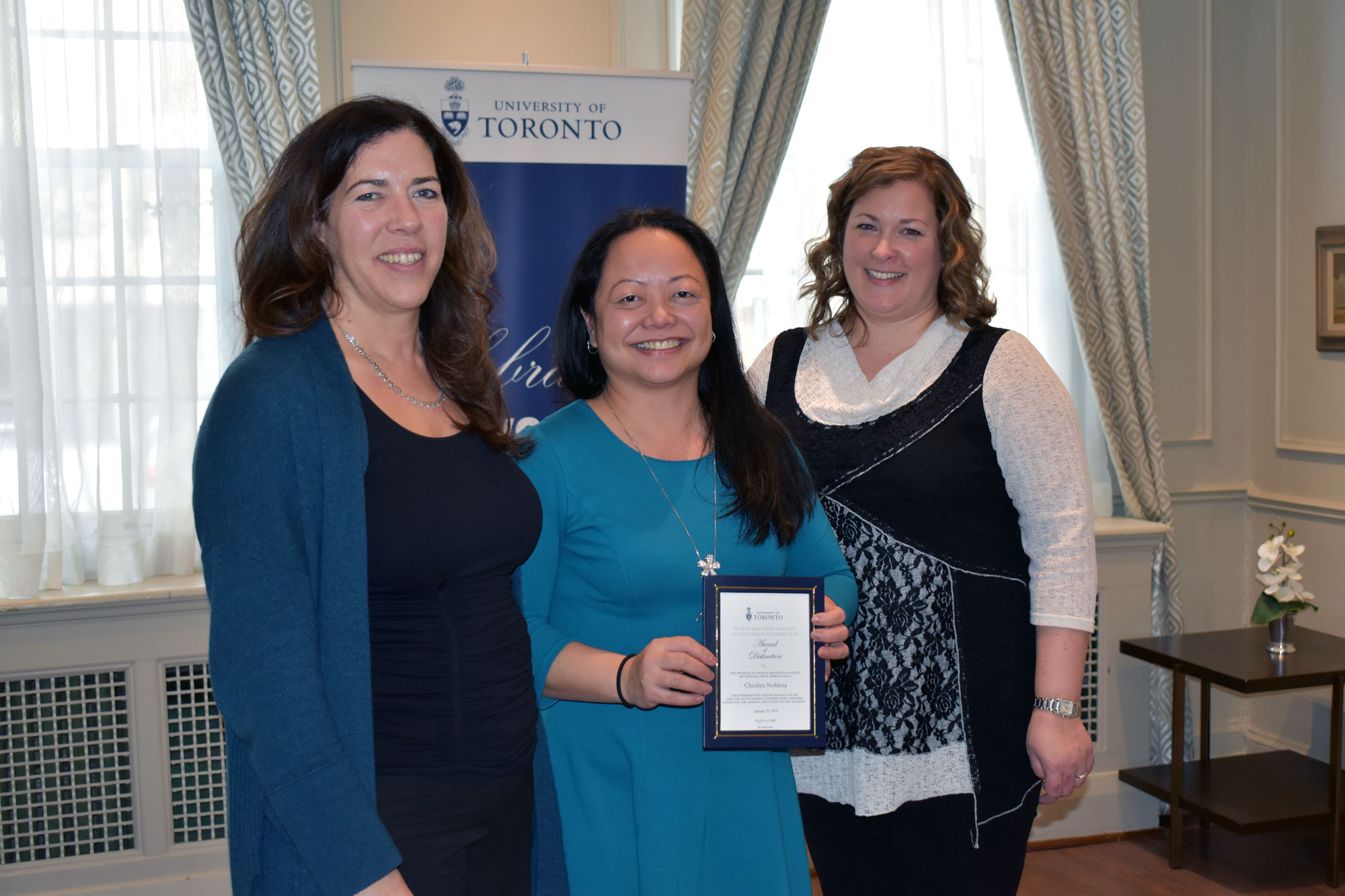 Cherilyn Nobleza poses with their HRE award of distinction with VP Kelly Hannah-Moffat and CHRO Erin Jackson