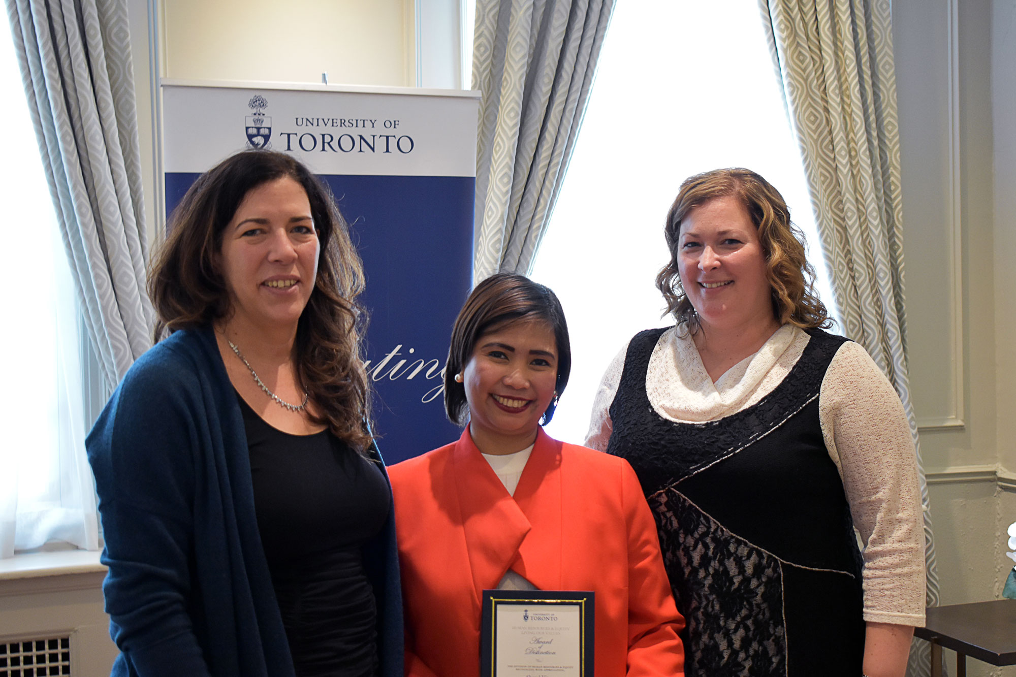 Sheryl Vitug poses with their HRE award of distinction with VP Kelly Hannah-Moffat and CHRO Erin Jackson